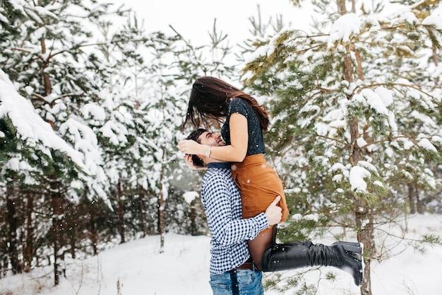 Hombre que detiene a la mujer en brazos en bosque del invierno