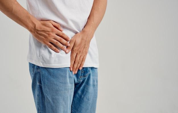 Hombre que experimenta dolor debajo del cinturón en la ingle y modelo de camiseta de jeans