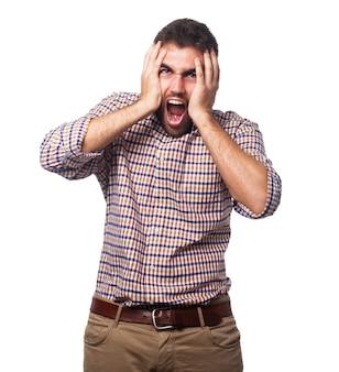 Hombre que grita enojado con las manos alrededor de la cabeza