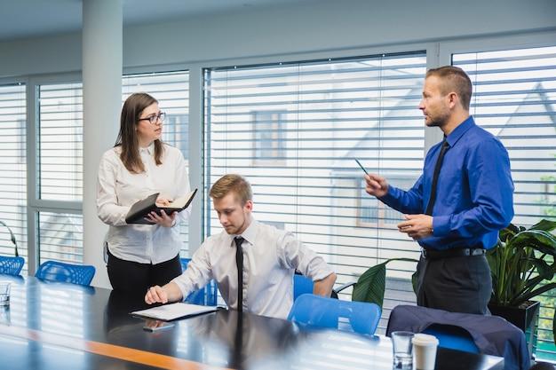 Hombre que habla con los compañeros de trabajo en la oficina