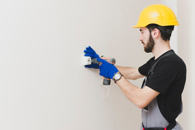 Hombre que instala el enchufe de pared con el arma de tornillo