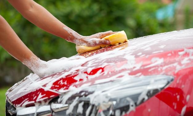 Hombre que lava el coche rojo con esponja y jabón