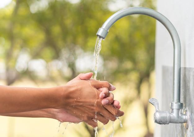 Hombre que se lava la mano después de trabajar con el fregadero exterior del grifo, limpiando el concepto de protección higiénica