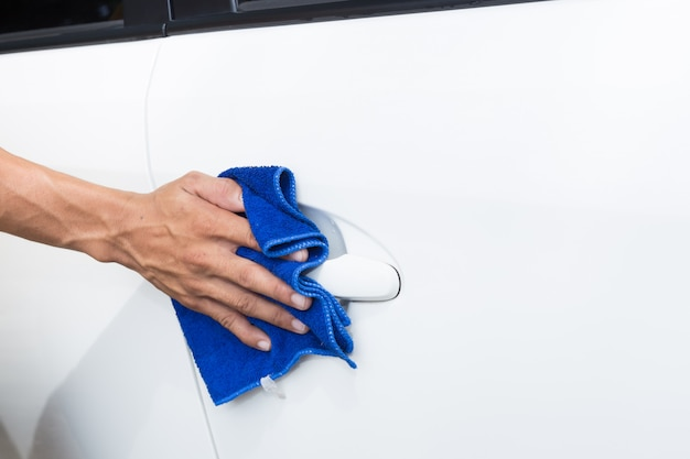 Hombre que limpia el automóvil con un paño de microfibra - conceptos de detallado y valeting del coche