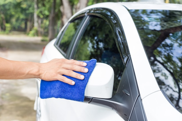 Hombre que limpia el coche con conceptos de limpieza y limpieza de coches de tela de microfibra