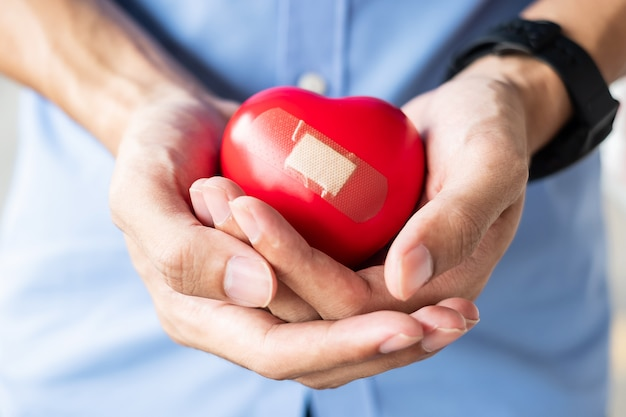 Hombre que lleva a cabo forma roja del corazón en fondo de madera. salud, seguro de vida