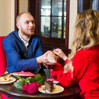 Hombre que lleva a cabo las manos de la mujer en la mesa en el restaurante