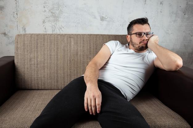 El hombre que lleva una camisa blanca yace en el sofá.