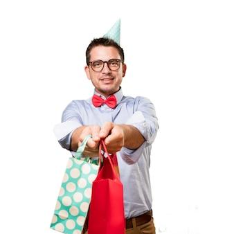 El hombre que lleva una pajarita y sombrero de partido rojo. celebración de regalo. ofrecimiento