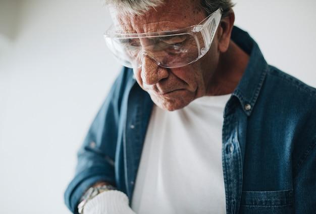 Hombre que llevaba gafas de seguridad mientras renovaba la casa.