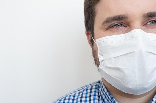 Hombre que llevaba una máscara para evitar gérmenes, humos tóxicos y polvo aislado en blanco