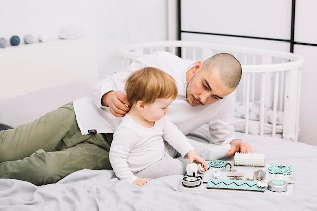 Hombre que miente cerca de pequeño bebé con el juguete que se sienta en cama