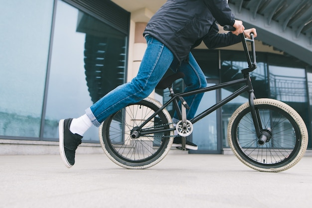 Un hombre que monta una bicicleta bmx en la ciudad en la arquitectura. ciclismo. cultura bmx