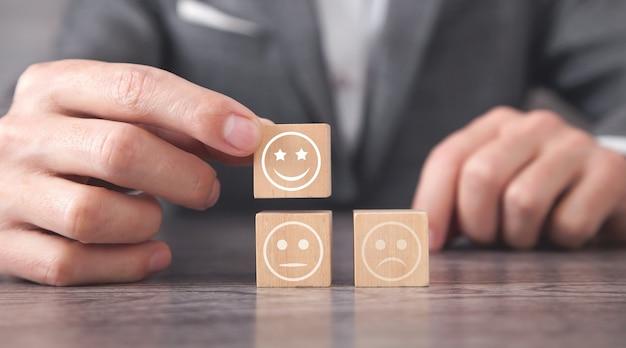 Hombre que muestra emoticonos tristes y felices en el cubo de madera. la satisfacción del cliente