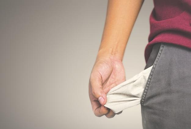 El hombre que muestra no tiene dinero al sacar el bolsillo.