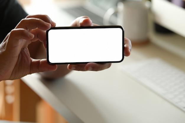 Hombre que muestra la pantalla en blanco del teléfono móvil en la oficina