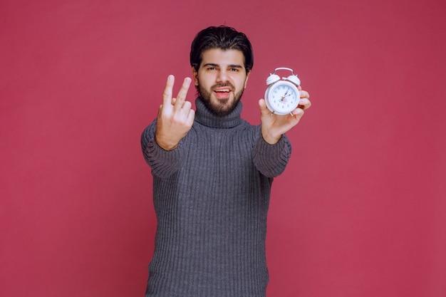 Hombre que muestra un reloj de alarma blanco y un punto de paking a una mejor oferta.