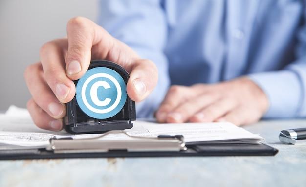 Hombre que muestra el símbolo de copyright. derechos de autor. propiedad intelectual