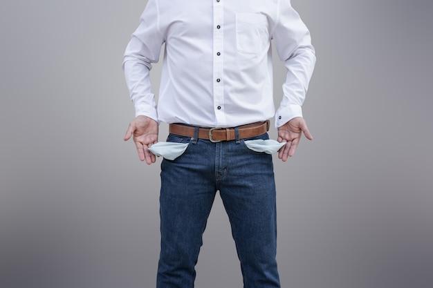 Hombre que muestra sus bolsillos vacíos en fondo de la pared.