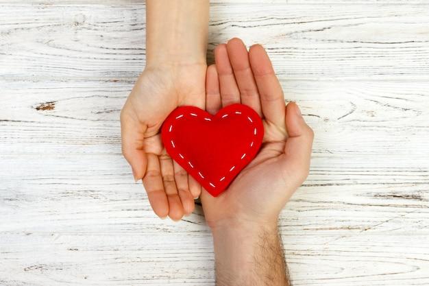 Hombre que ofrece un corazón blanco con ternura a una mujer. concepto del día de san valentín en un fondo de madera, vista desde arriba