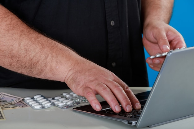 Hombre que ordena medicamentos o suplementos de una farmacia de internet una computadora portátil que investiga
