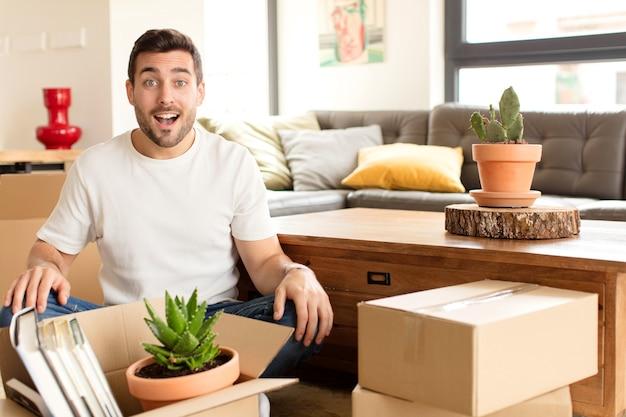 Hombre que parece feliz y gratamente sorprendido, emocionado con una expresión fascinada y conmocionada