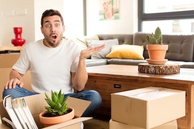 Hombre que parece sorprendido y conmocionado, con la mandíbula caída sosteniendo un objeto con una mano abierta en el costado