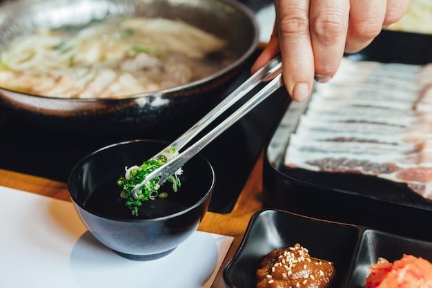 Hombre que pellizca la cebolleta picada en salsa ponzu con pinzas para mojar con cerdo kurobuta.