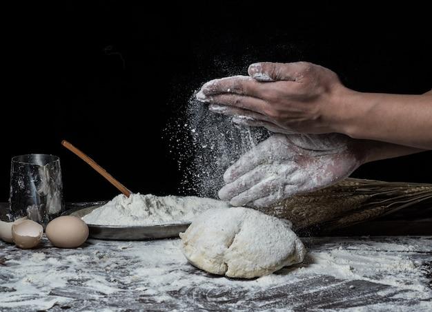 Hombre que prepara la masa de pan en la tabla de madera en un cierre de la panadería para arriba