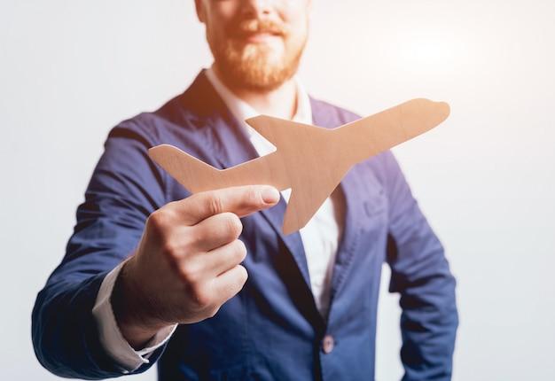 Hombre que propone firmar una póliza de seguro de vida, el agente está sosteniendo el modelo de avión de madera.