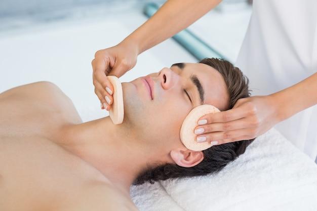 Hombre que recibe masaje facial en el centro de spa