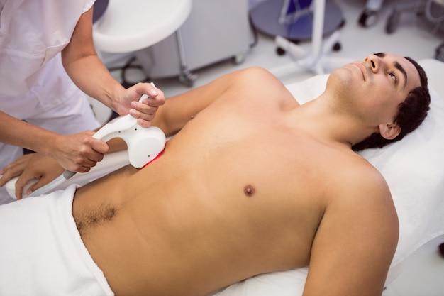 Hombre que recibe tratamiento de depilación láser