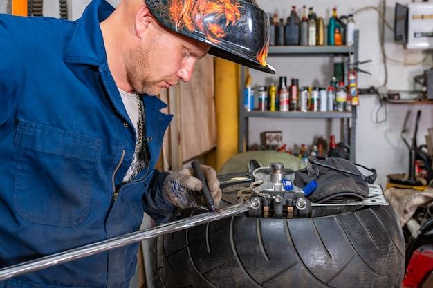 El hombre que repara el neumático de la motocicleta con un kit de reparación, un kit de reparación de tapones para neumáticos sin cámara.