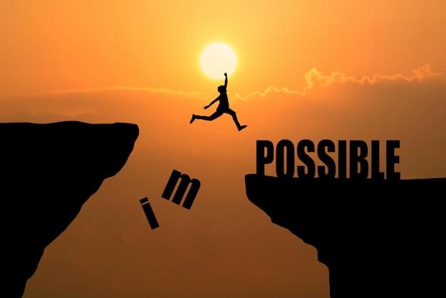 Hombre que salta sobre imposible o posible sobre acantilado en fondo de la puesta del sol, idea del concepto del negocio