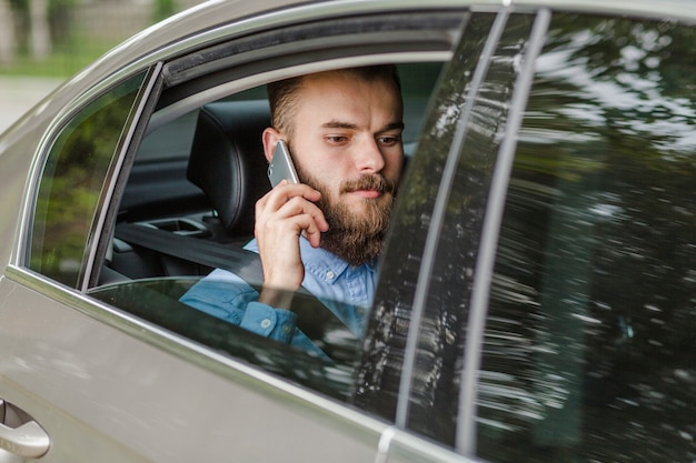 Hombre que se sienta dentro del coche usando el teléfono celular