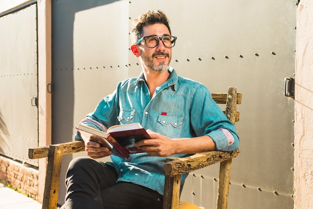Hombre que se sienta en la silla que sostiene el libro en la mano que mira lejos
