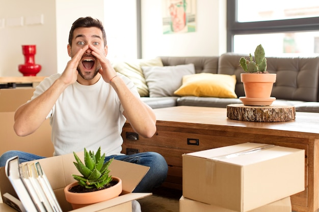 Hombre que se siente feliz, emocionado y positivo, dando un gran grito con las manos al lado de la boca, gritando
