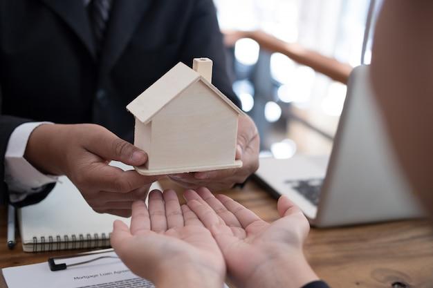 Hombre que solicita un préstamo hipotecario con un empleado del banco.