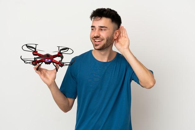 Hombre que sostiene un avión no tripulado aislado sobre fondo blanco escuchando algo poniendo la mano en la oreja