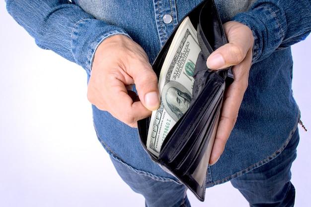 Hombre que sostiene la billetera con dinero de dólares en fondo blanco con trazado de recorte