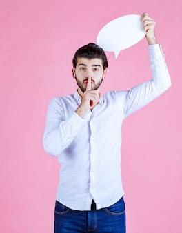 Hombre que sostiene un bocadillo de diálogo ovale y apunta al silencio.