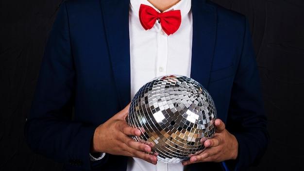 Hombre que sostiene la bola de discoteca