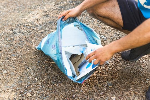 Hombre que sostiene la bolsa de basura plástica
