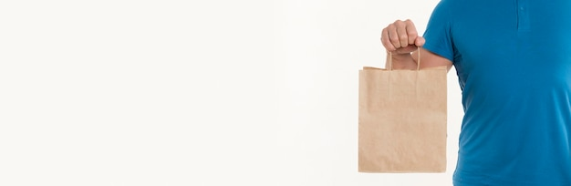 Hombre que sostiene la bolsa de papel con espacio de copia