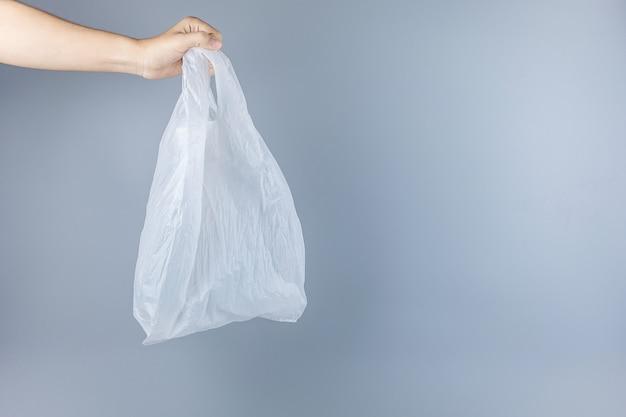 Hombre que sostiene la bolsa de plástico con espacio de copia de texto. protección del medio ambiente, cero residuos, reutilizable, decir no plástico, concepto del día mundial del medio ambiente y del día de la tierra