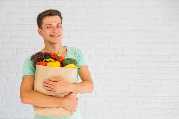 Hombre que sostiene la bolsa de supermercado llena de frutas y verduras guiñando un ojo