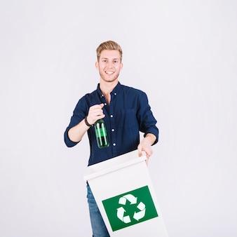 Hombre que sostiene la botella y el cubo de basura con el icono de reciclaje