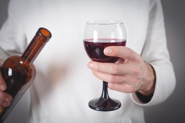 Hombre que sostiene la botella de vino tinto y el vidrio.