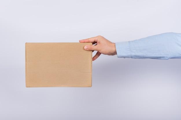 Hombre que sostiene la caja con el brazo extendido. caja de cartón. entrega de paquetes. vista lateral.