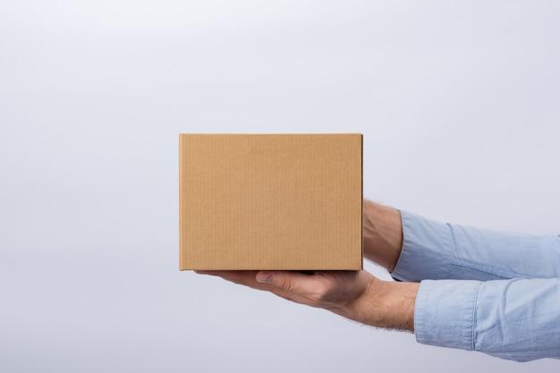 Hombre que sostiene la caja con el brazo extendido.